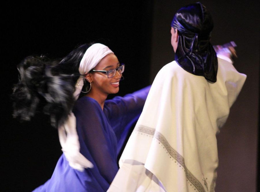 Strut your stuff: Sophomore Maryam Abdirahman dances with her partner in the fashion show portion of the multicultural performance.