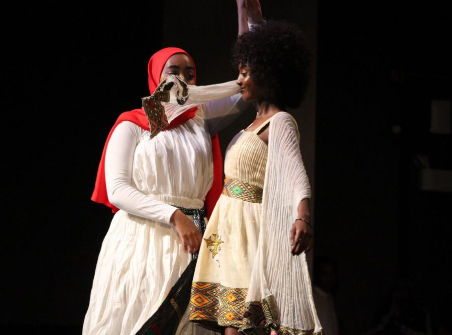 Junior Illhan Abdi spins senior Aisha Abdi around to display cultural dress. Abdi participated in the fashion show as well as read out loud a poem.