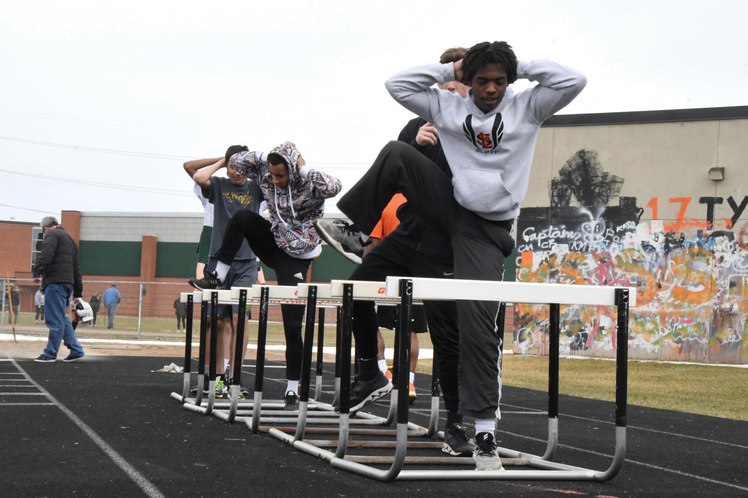 Senior Donovan Hill practices with his fellow track teammates by walking over hurdles before running. The recent snowstorm April 11 caused the team to again be indoors.