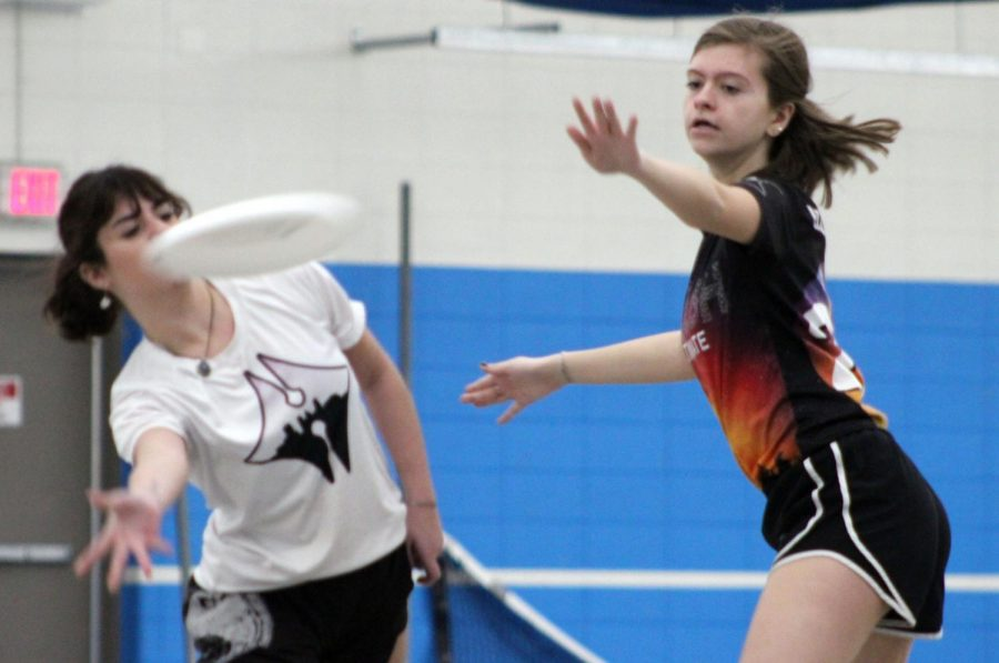 Junior Sarah Wojtasiak attempts to block throw at scrimmage against Hopkins Feb. 26. Due to bad weather affecting playing fields Girls ultimate have had more indoor games than outdoor.
