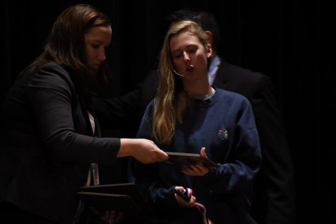 Assistant Principle Jessica Busse hands senior Natalie Aune her academic award during the academic awards ceremony.