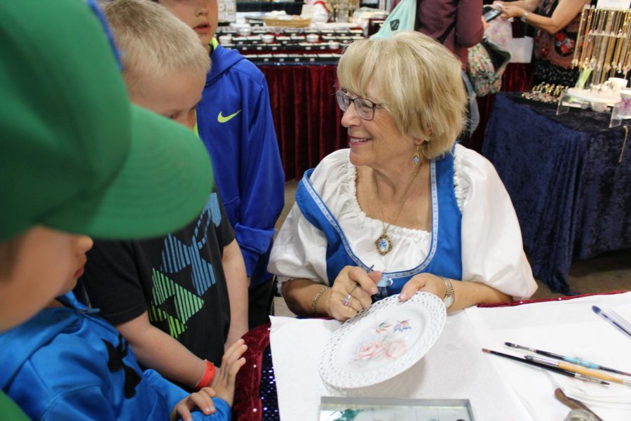 A Germain porcelain painter shows her work to elementary school kids on a field trip. Various pieces of artwork, including earrings, necklaces and plates were available for sale.