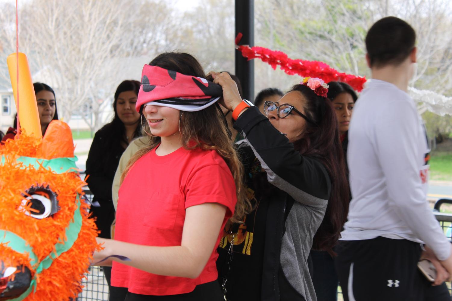Multicultural liaison Carmen Rudin blindfolds junior Victoria Caraballo as she prepares to hit the piñata during the celebration May 2. The group celebrated during fifth hour May 2.