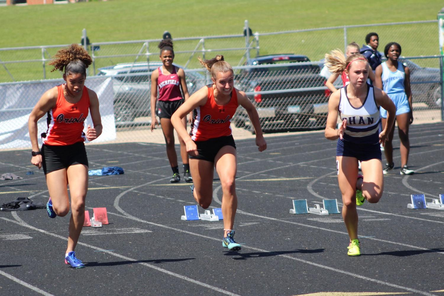 Freshman Freya Wade and junior Ava Bishop run the 100 meter during Sections May 15. The girls' track and field team were Section champions.