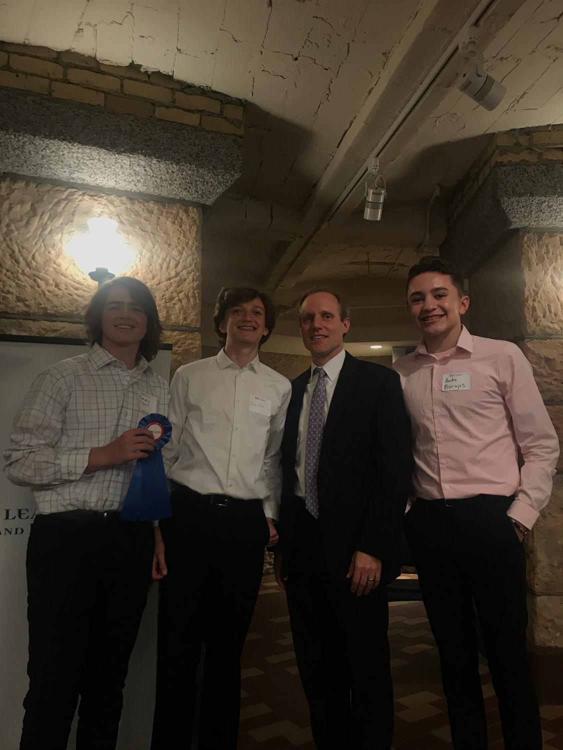 Freshmen Tommy Tight, Adam Gips and Andre Barajas pose with Minnesota Secretary of State Steve Simon. Freshman civics students were selected to present their Project Citizen poster boards at the state capitol May 15.