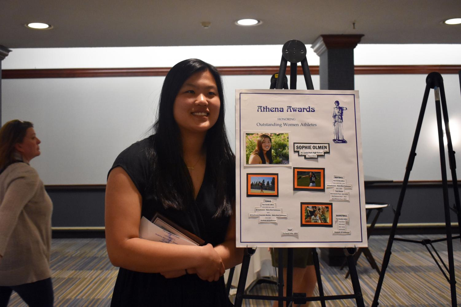 Senior Athena award recipient Sophie Olmen poses for a picture by her poster board that contains information on her athletic acheivemnets during her high school career.