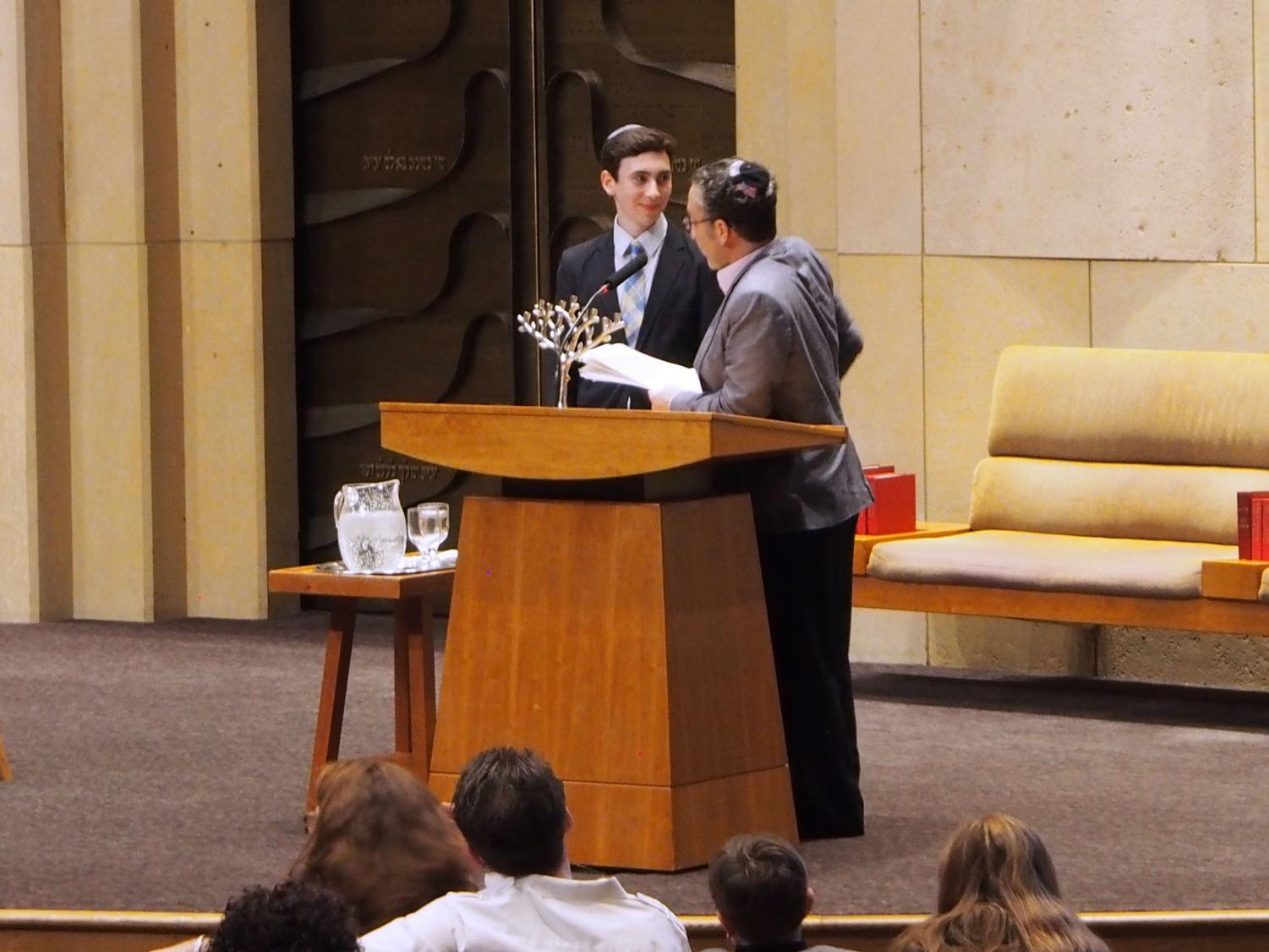 Senior Yonah Davis accepts his Howie Stillman Young Leadership Award from Joel Glaser at Adath Jeshurun Synagogue. The award is given annually to young, Jewish leaders who are active in a Twin Cities' youth group.