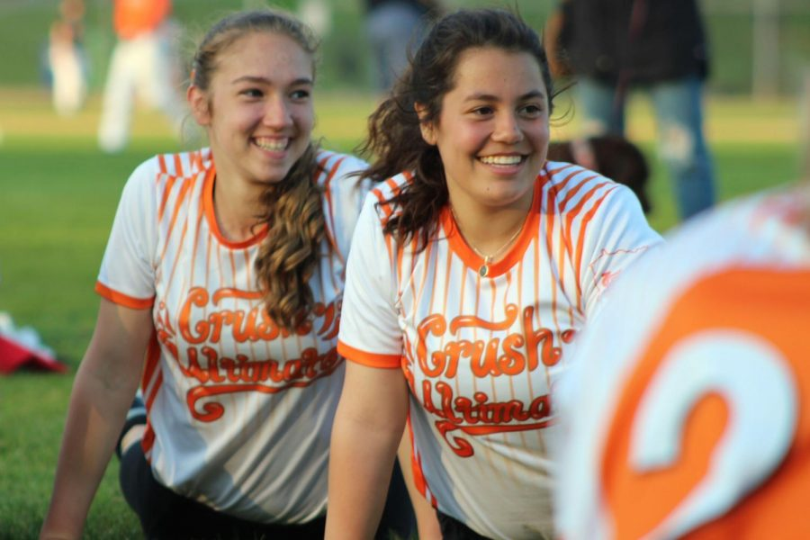 Juniors Lauren Schmelzer and Maggie Klein laugh with the team while stretching.