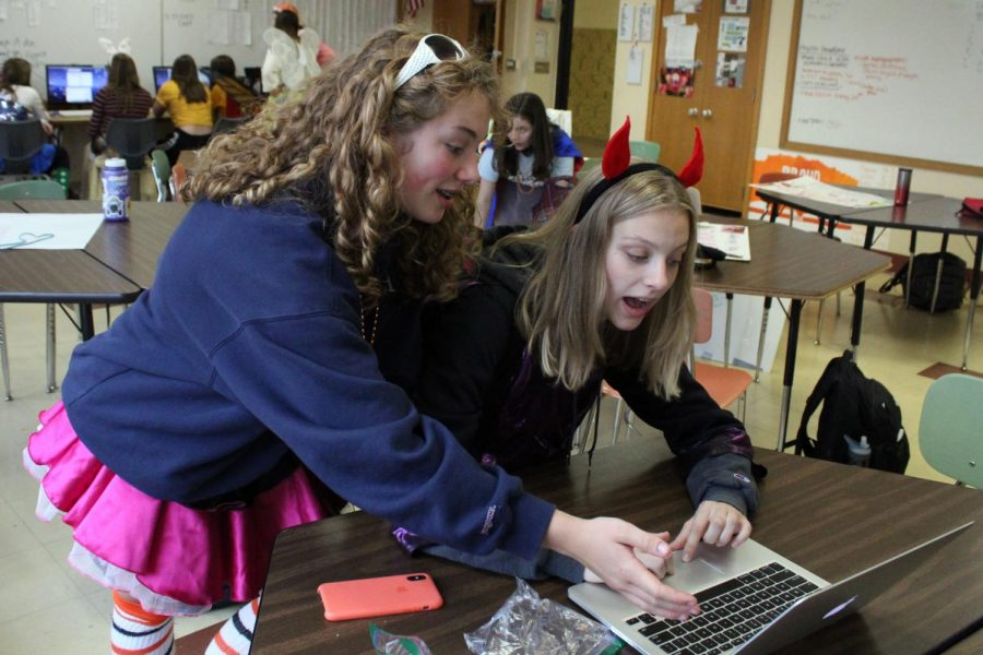 Sophomores Evie Gutzke and Anna Jensen discuss over a story. Gutzke will be an upcoming design editor and Jensen will be a copy editor for the yearbook next year.