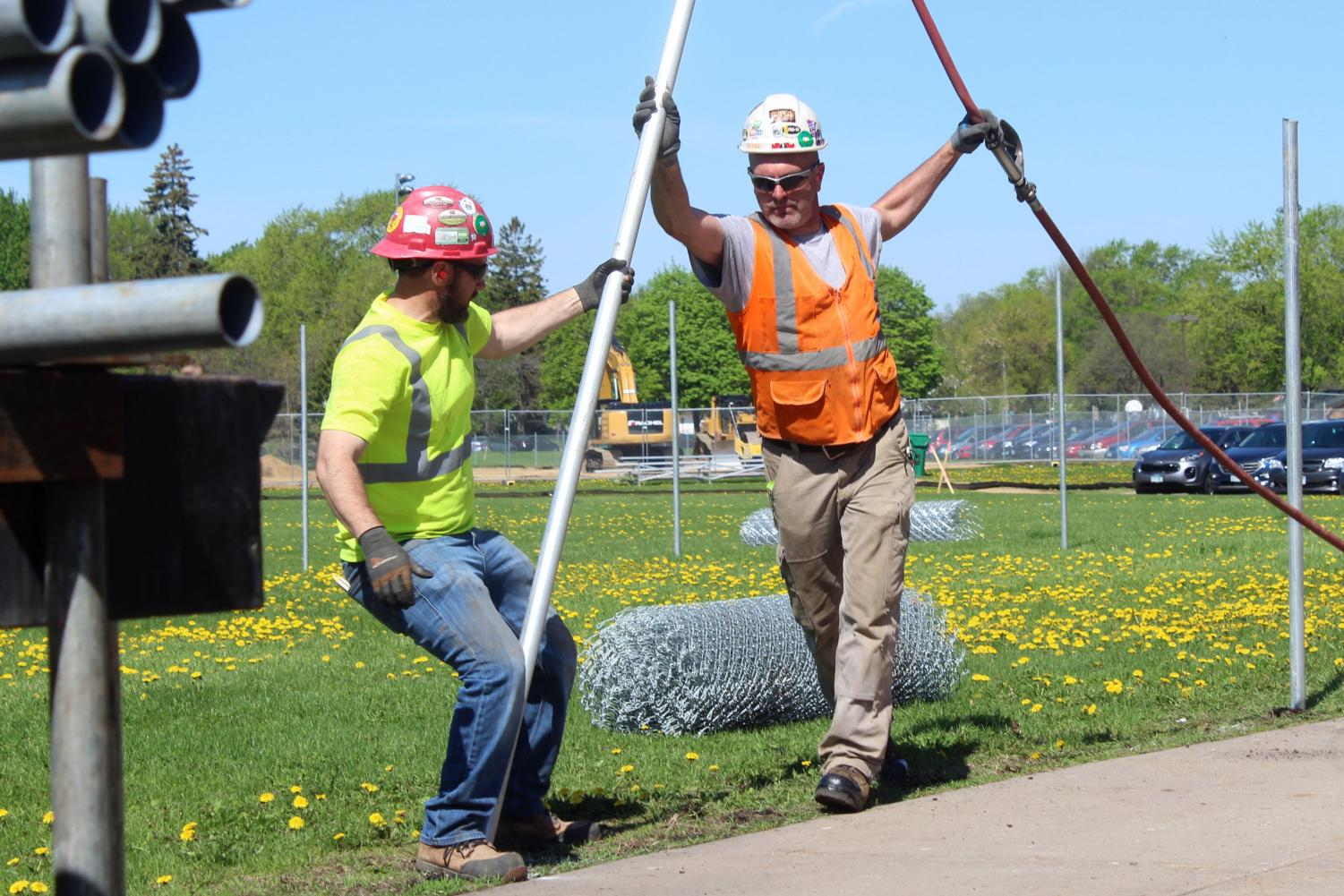 Construction workers place a poll that will be part of the fence surrounding the construction of the new fitness center. The fence went up May 16 in addition to reconstruction of the tennis courts and locker rooms.