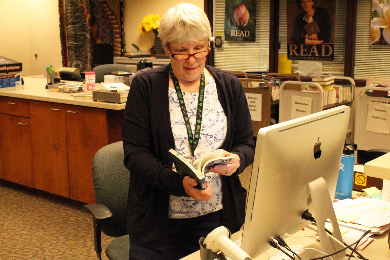 Librarian Ellen George goes through a book making sure everything is in good condition. You can find Ms. George in the Media Center at the front desk.
