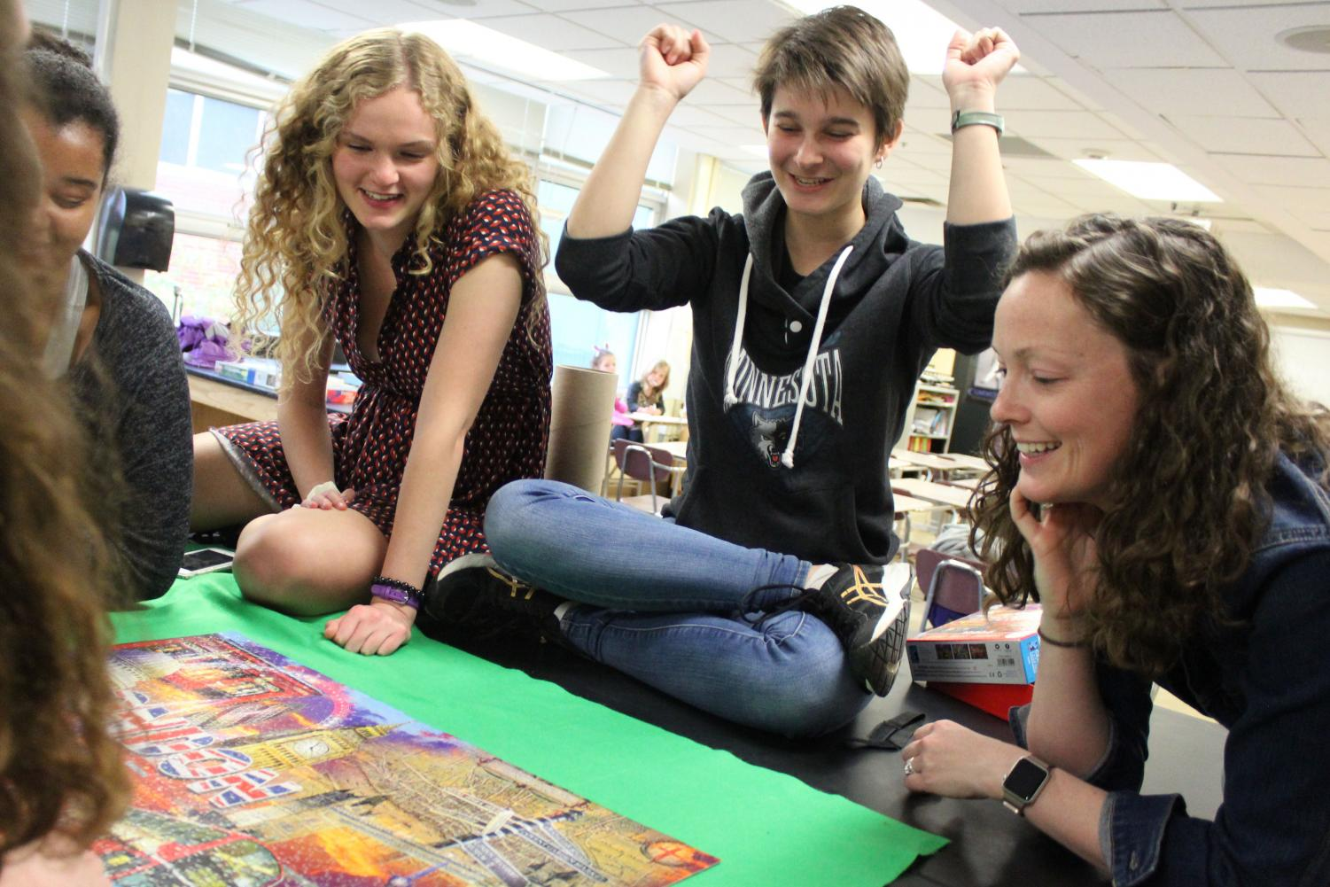 Senior Greta Long rejoices after placing the last piece in the puzzle at puzzle club May 23. Puzzle clubs leaders are seniors, and do not have a plan for next year, according to Long.