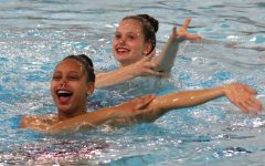 Sophomore Bella Steward and junior Isabel Kjaer smile while swimming their Brittany Spears duet at free rehearsal May 14. Steward and Kjaer placed second in the extended division for duets at Sections which took place May 18.