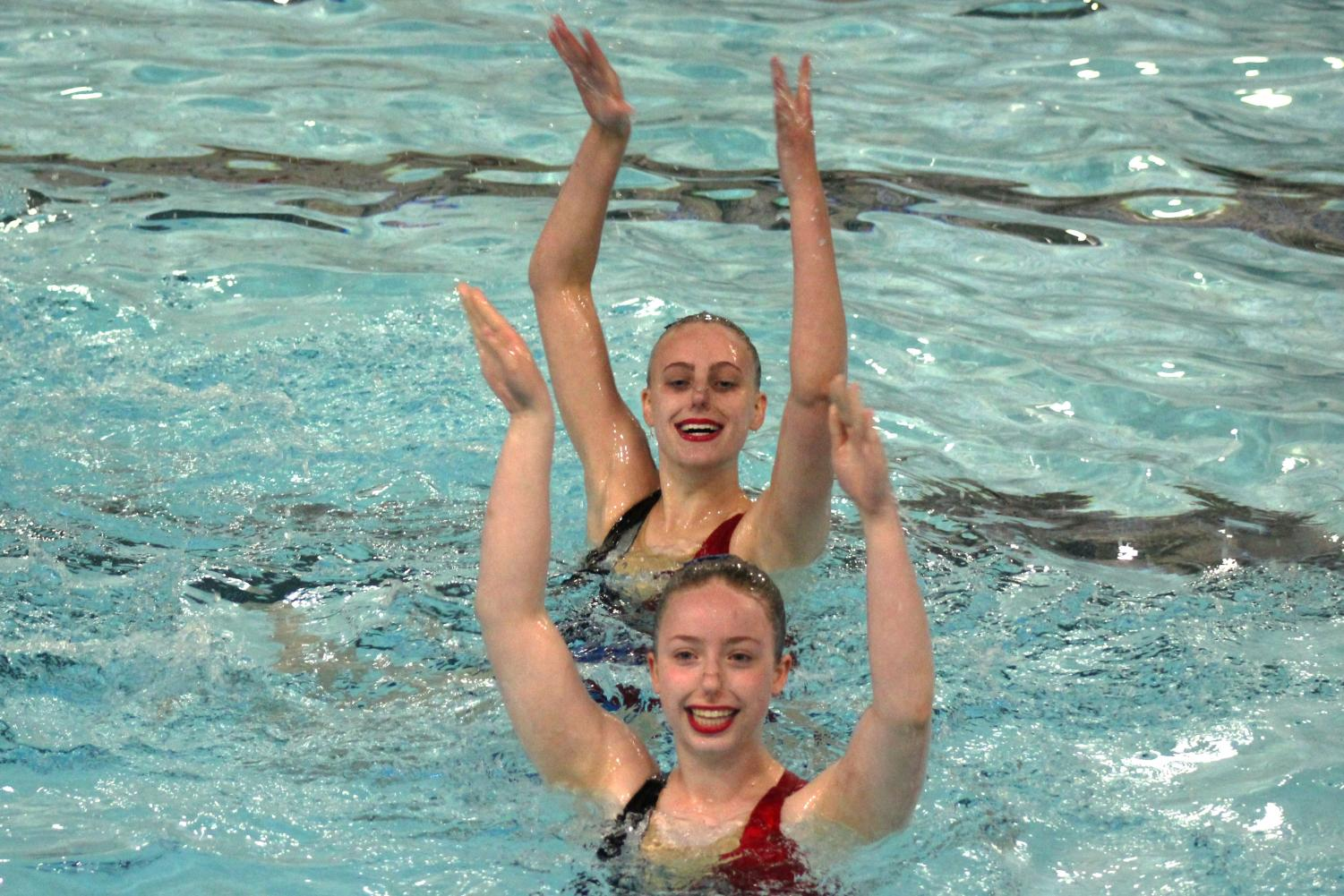 Juniors Ava Tronson and Annie Breyak smile as they perform their team routine at Sections. The routine placed first in the extended team division at Sections, May 18.