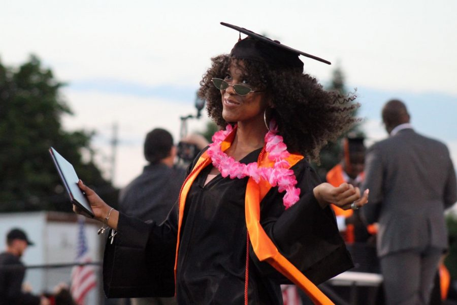 Graduate Brenda Givens reacts after walking across the stage to recieve her diploma at Graduation June 6.