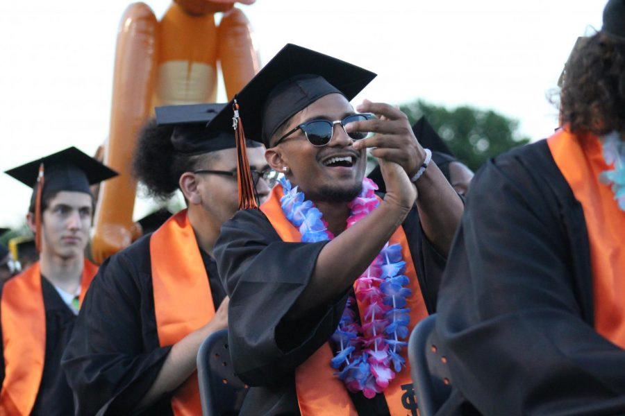 Senior Ajai Datt claps for his friend on stage at Graduation.