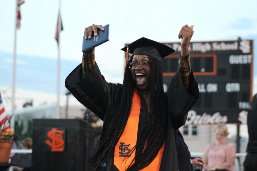 Jamelia Addison celebrates after walking across the stage to receive her diploma.