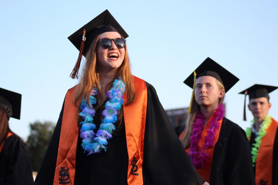 Anastasia Armbrecht smiles at family and friends in the stands as they watch her walk to their seats.