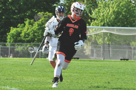 Junior Flynn Spano cradles the ball with his stick while running the ball toward the opponent