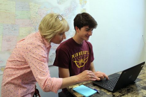 Career and College Coordinator Kara Mueller helps senior Brett Duncan find a summer job June 3. Mueller has a board with all the summer jobs available in St. Louis Park outside her room in B220.
