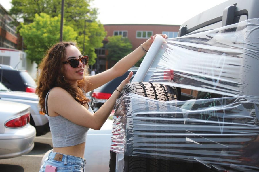 Senior Natalia Caraballo wraps a car in saran wrap on senior ditch day May 31. Many of the senior ladies met that morning to write on cars as a way to leave their final mark on the school before they graduate. Seniors will be graduating at 7:30 p.m. June 6 at the stadium.