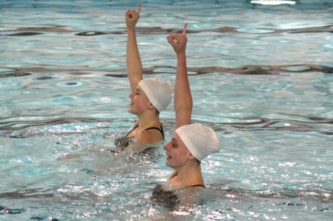 "Juniors Annie Breyak and Ella Hammerstrand hold up their pinky fingers during the song ""24K Magic"" in their Bruno Mars duet during a routine meet against Bloomington, May 3."