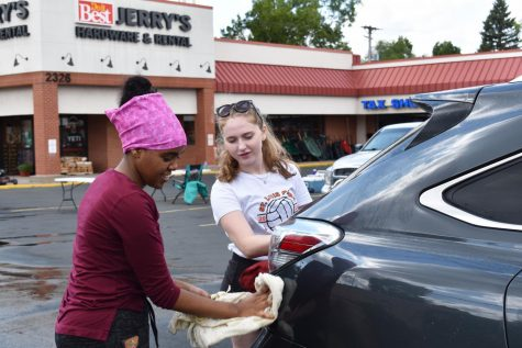 Sophomore Lily Nugteren and junior Helen Tefera dry off a car at the carwash fundraiser Aug. 25. The fundraiser was held at Jerry's Hardware Store on Louisiana Ave.