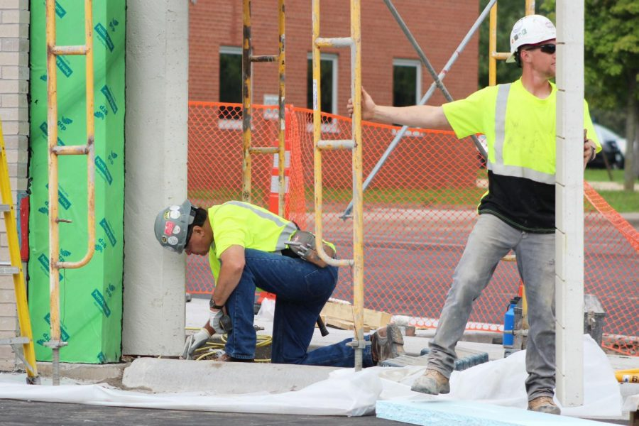 Construction workers finish putting in a wall at the north entrance Aug. 26. Construction has progressed through the summer and will not disrupt students learning once school begins.