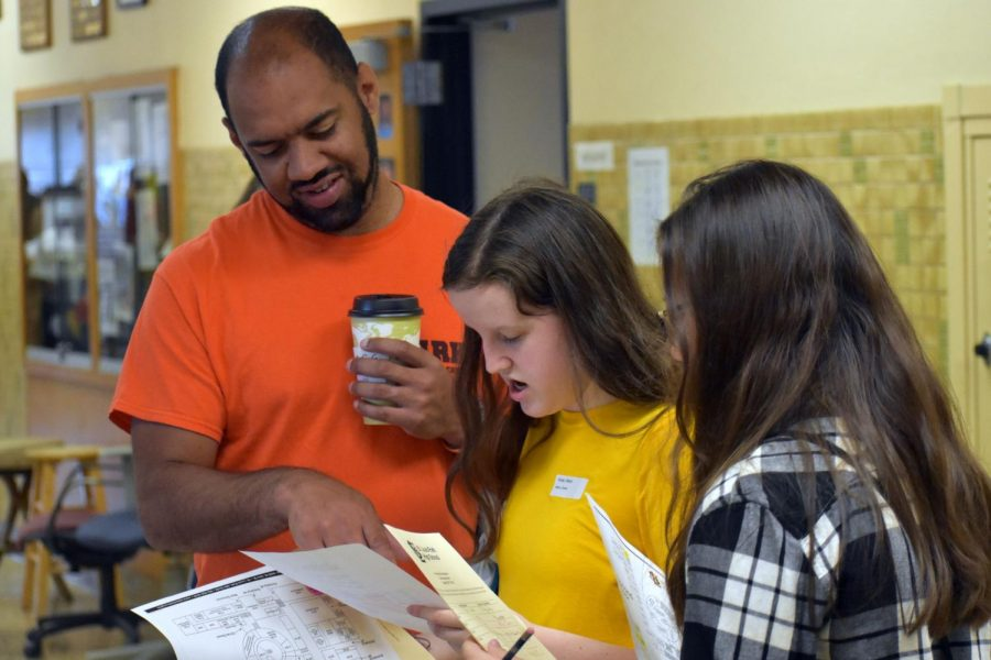 Math+teacher+Anson+Opara+helps+two+students+locate+their+classes.+Students+were+encouraged+to+walk+around+the+school+in+order+to+familiarize+themselves+with+their+schedules+and+the+building.