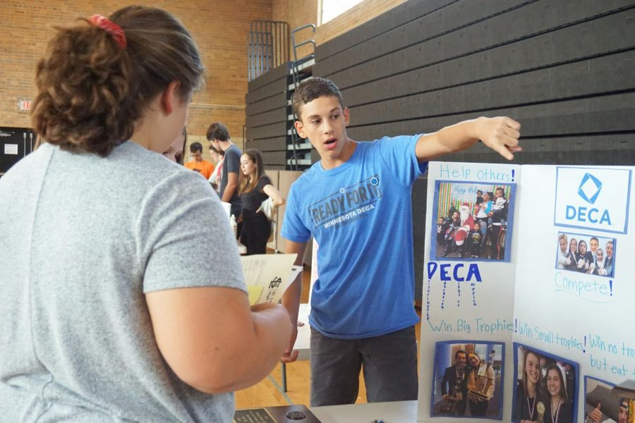 Junior Koby Davis promotes DECA to incoming freshmen at the activities fair Aug. 28. Freshmen also met their advisors, learned their way around the high school, and found their classrooms.