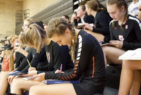 Freshman volleyball player Katie Crocker completes her homework in the stands of a varsity volleyball game Sept. 10. Many student athletes have a difficult time finishing their homework during their primary sports seasons.