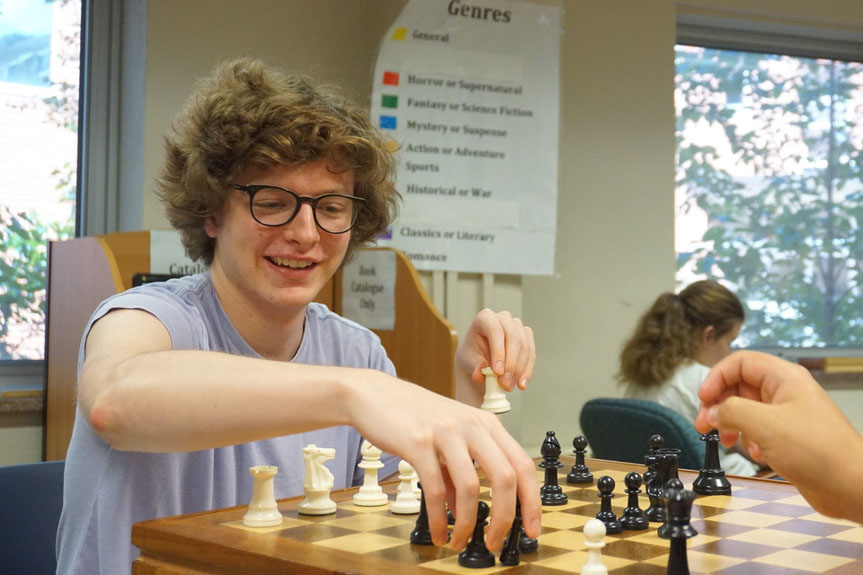 Senior+Mitchell+VonEschen+plays+chess+in+the+LMC+during+the+carnival.+Other+activities+were+scattered+around+the+school+building%2C+as+well+as+outside.