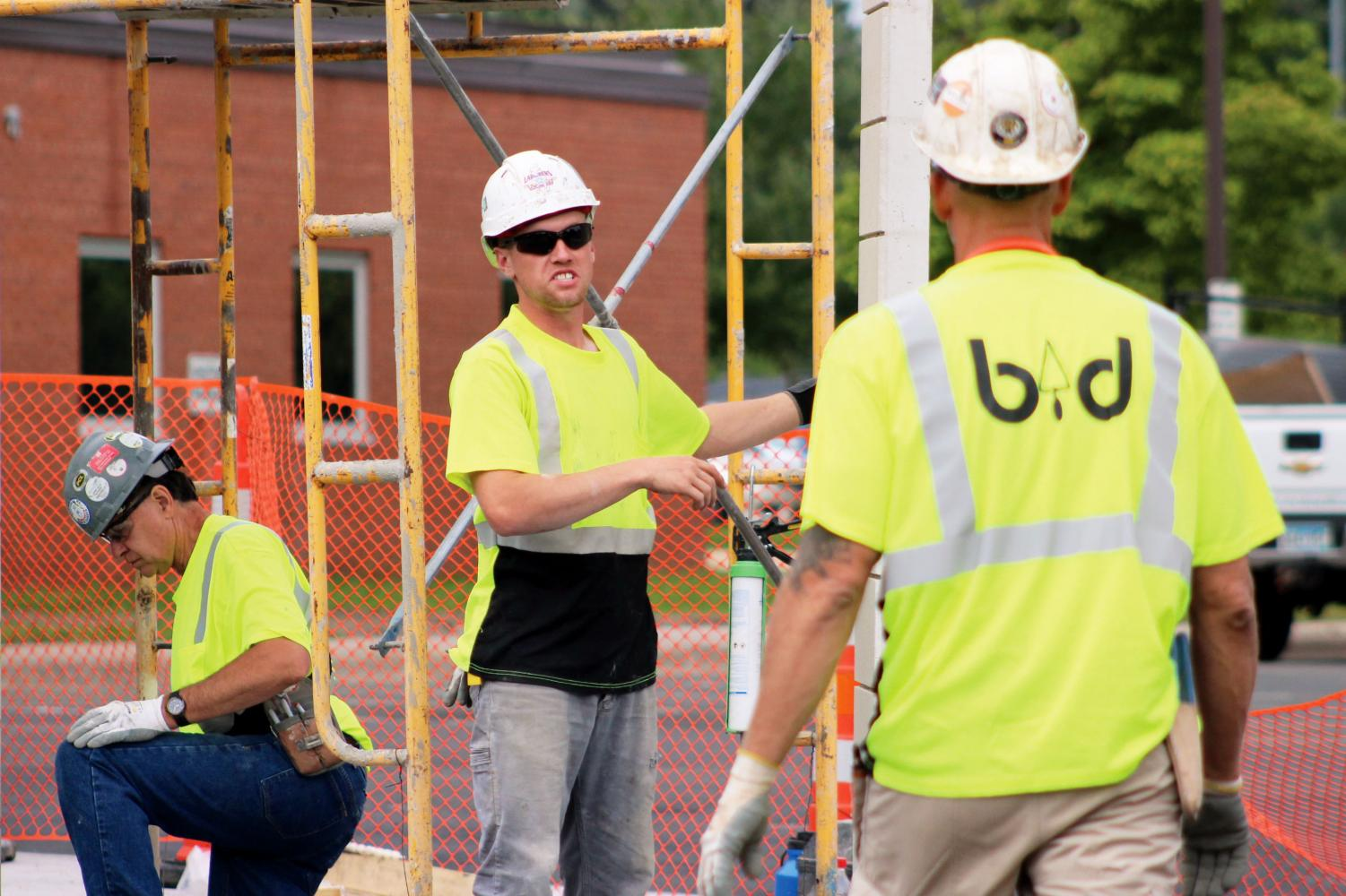 Construction workers finish putting in a wall at the north entrance Aug. 26. According to Thomas Bravo, construction has progressed through the summer and will continue on the fitness center throughout the school year.