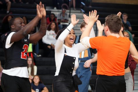 Members of the Homecoming court celebrate after scoring a point at the teacher versus Homecoming court volleyball game. Court members were announced Sept. 13 at a previous Pep fest.