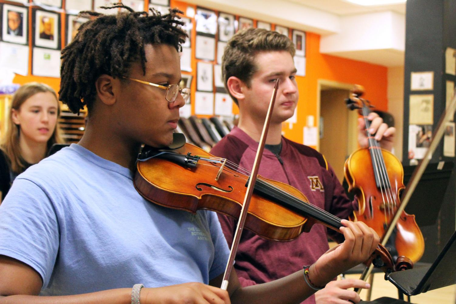Freshman Meshach Mandel pulls his bow across the strings on his violin during third hour Sept. 20. Orchestra is working toward its Halloween concert Oct. 30.
