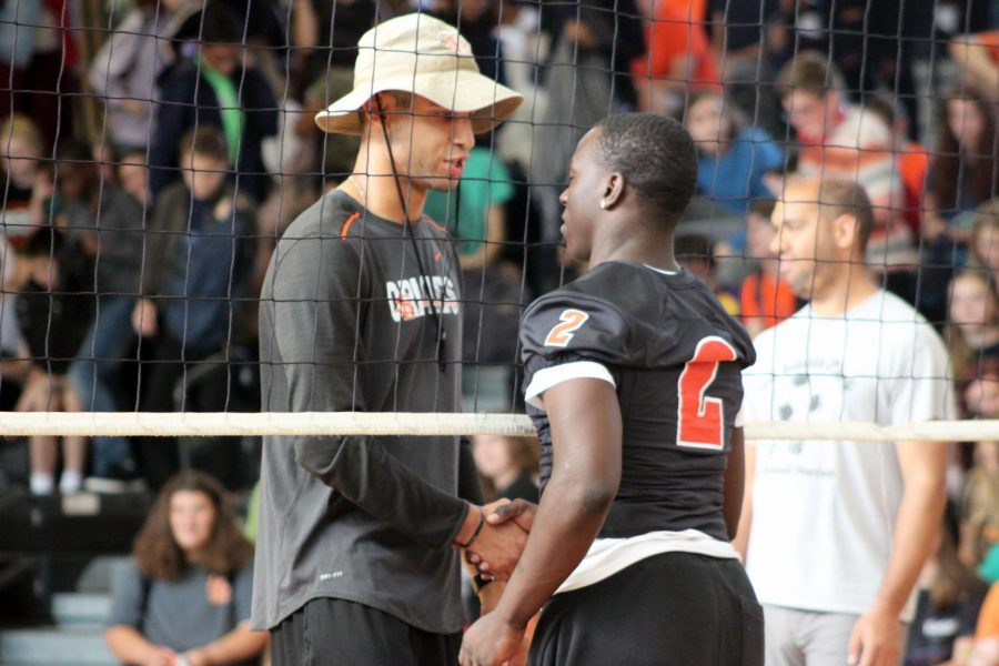 Science teacher Alexander Polk shakes hands with senior Tobyous Davenport. Teachers from all departments formed a team to play volleyball against the Homecoming court.