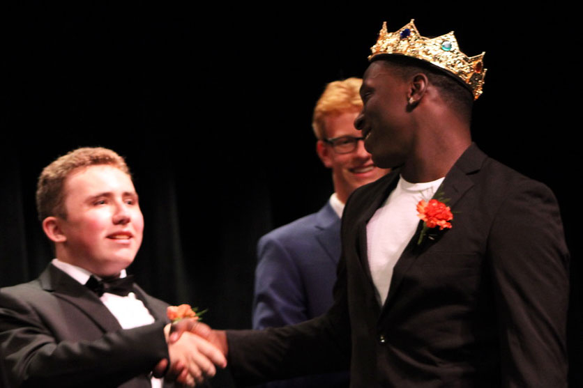 Senior on the Homecoming court Ryan Erickson shakes senior Tobyous Davenport's hand in congratulations after Davenport was crowned Homecoming king.