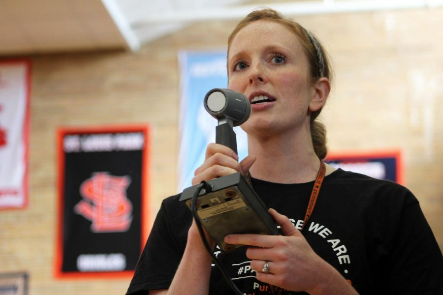 English teacher Lindsey Meyer speaks at the Pep fest over the loudspeaker system. The Pep fest included a teacher versus Homecoming court volleyball game.