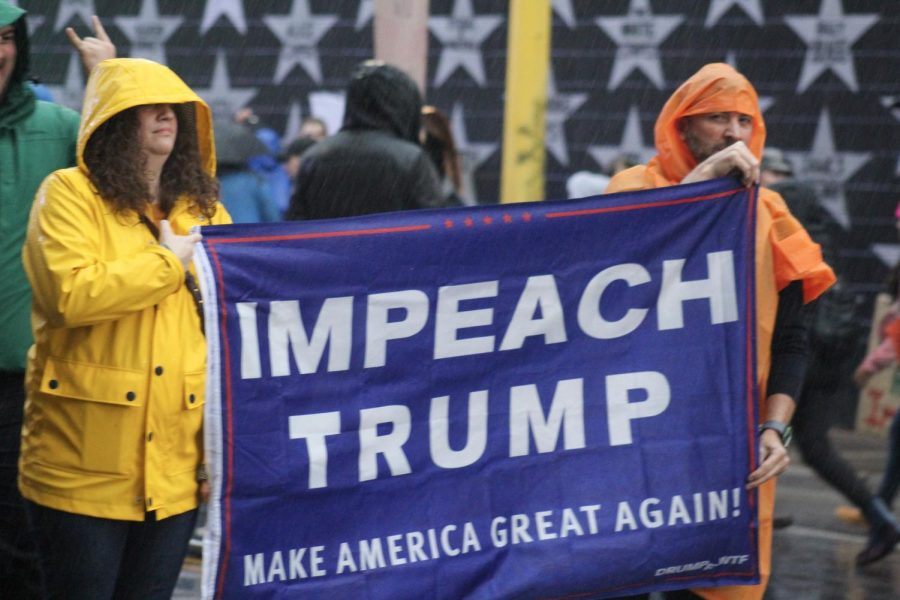 Two people carry an Impeach Trump flag. The anti-Trump protest was organized in response to the Trump rally hosted Oct. 10 at Target Center.