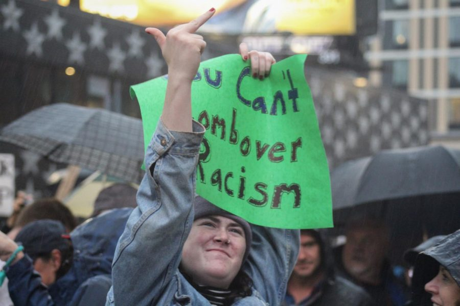 """A woman flips off the line waiting to get into the Trump rally. She holds a sign that reads, """"You can't combover racism."""""""
