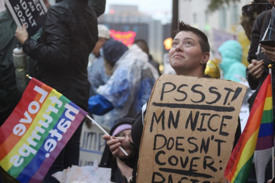 """A protester waves a """"love trumps hate"""" flag and holds a sign that reads, """"Psst! MN Nice doesn't cover: racism"""" at the anti-Trump protest Oct. 10 in front of Target Center."""