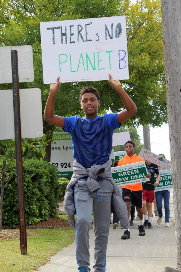 """Seventh grader Micah Curtis leads the climate march of 37 people Sept. 27 to City Hall. He carried a sign reading """"There's no planet B."""""""