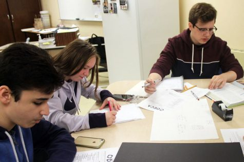 Juniors Kahrder Schmitt and James Peterson work on a project for DECA Oct. 22. Sophomore Julian Johnson also works on a DECA related task.