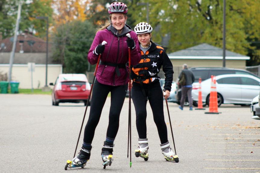 Juniors Olivia Etz and Mimi Kniser roller ski down the parking lot at captains practice Oct. 28. Practices are led by captains senior Ella Hammerstrand, Isabel Kjaer, David Klein, Maggie Klein, Rakesh Plantz, and junior Danny Walsh.