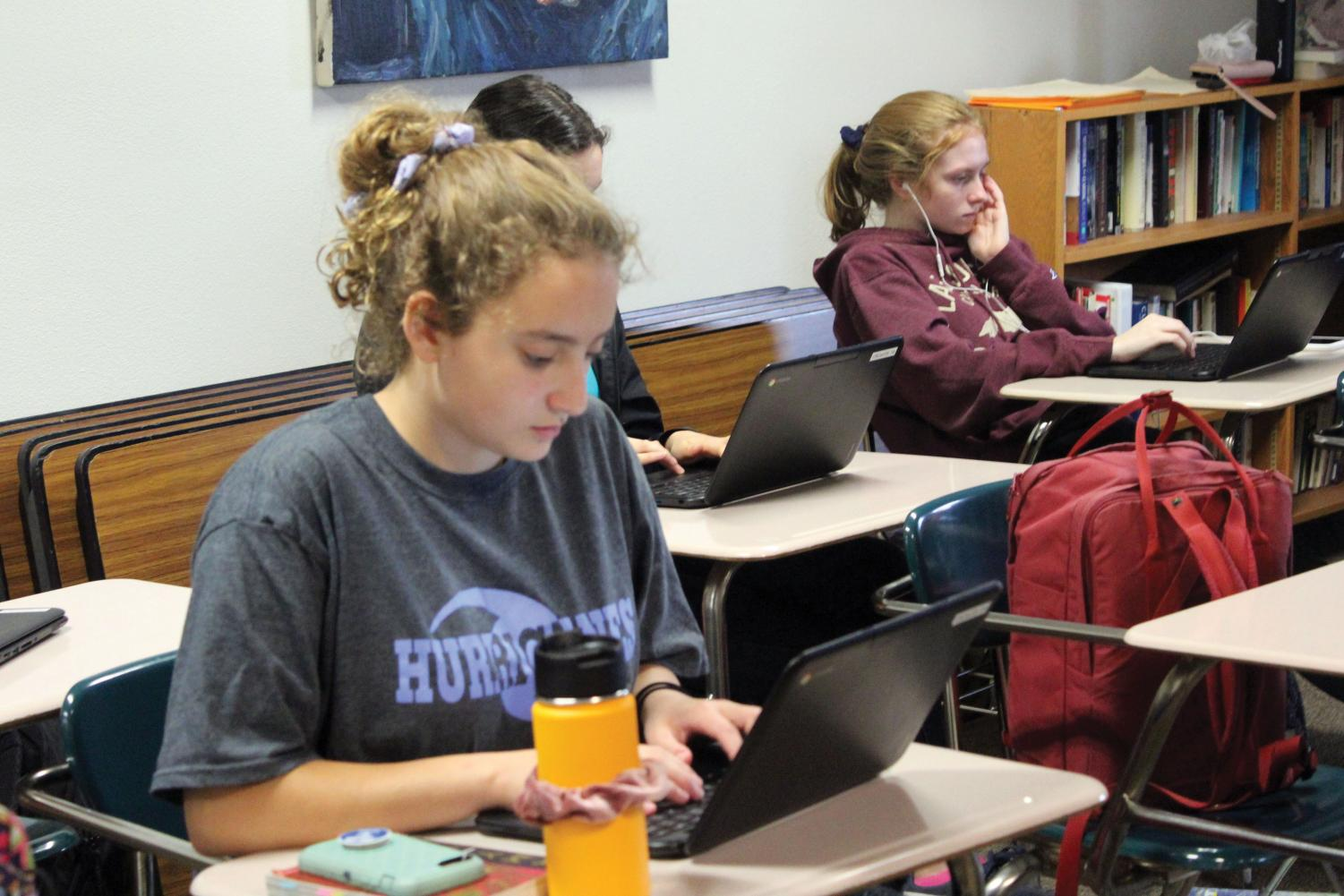 Juniors Julia Salita and Liz Madigan work on an online assignment in English teacher Andrew Wilkes's class Oct. 3. Wilkes works to go paperless this school year.