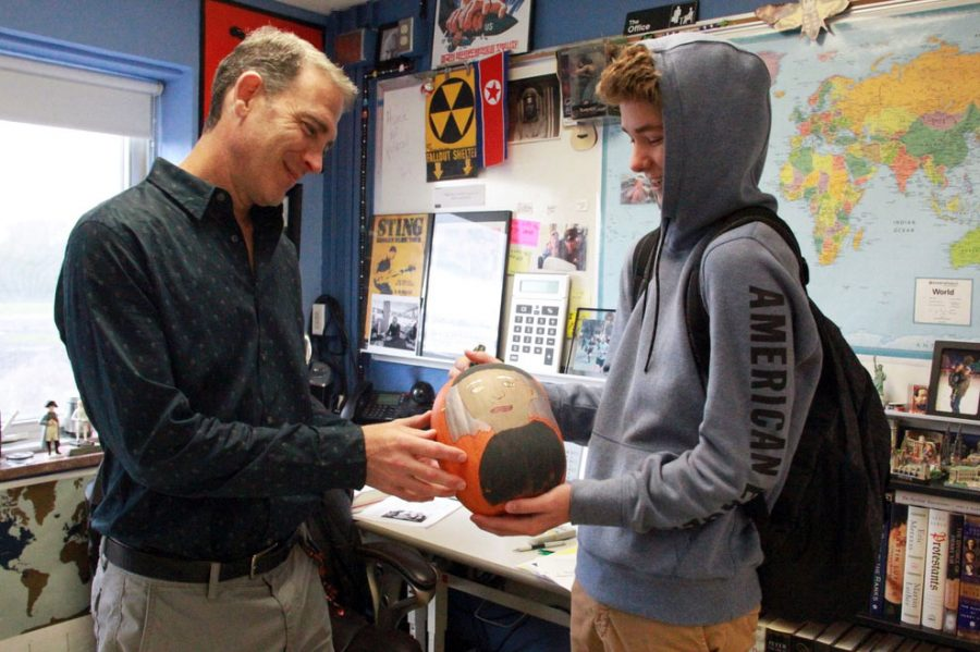 Sophomore Oliver Smith turns in an extra credit project to AP European History teacher Jeffrey Cohen Oct. 24. AP European History students are given the opportunity to paint historically themed pumpkins for extra credit.