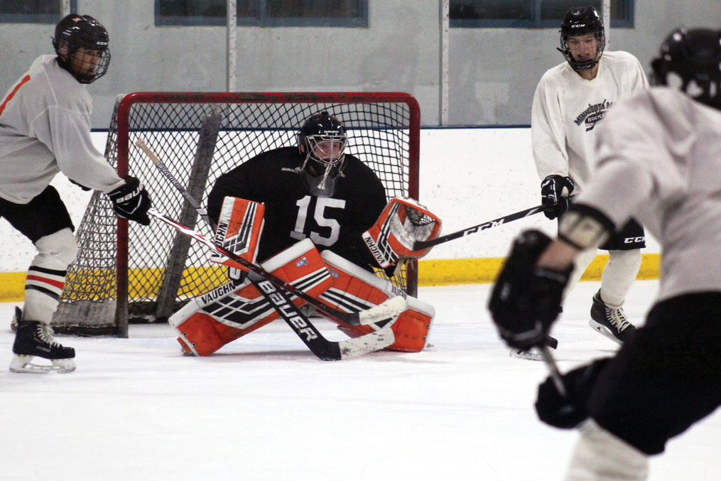 Senior Will Pinney blocks a shot on goal during a shooting drill at practice Sept. 23. For every shot Pinney blocks during his hockey games, he raises money to help women dealing with breast cancer.