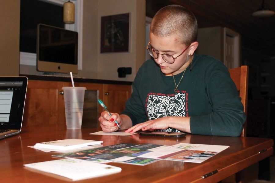 Senior Maddie Lind writes postcards to St. Louis Park residents informing them about the upcoming election. Lind is campaigning for Larry Kraft along with several other students.
