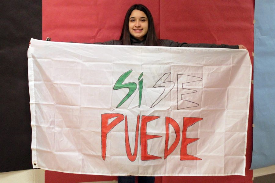 Ms. Cisco supervises a student run project for students to represent themselves with flags. Senior Andrea Martinez proudly holds a flag representing her culture.