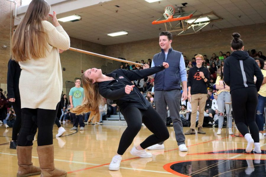 Senior Makaila Winward takes part in a round of limbo at a pep fest along with the rest of the volleyball team. Each member of the team was introduced and cheered on by the school the day leading up to the game.